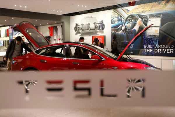 Seorang pria melihat Tesla Model S di showroom di Beijing, China - REUTERS
