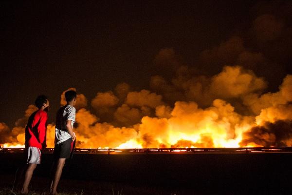 Warga menyaksikan kepulan asap api yang membakar gudang kapas PT Sri Rejeki Isman Tbk. (Sritex) di Sukoharjo, Jawa Tengah, Jumat (27/9/2019). - ANTARA FOTO/Mohammad Ayudha