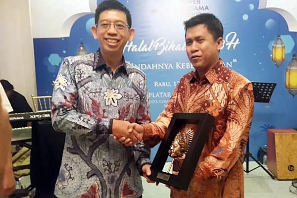 Direktur PT Tower Bersama Infrastructure Tbk Helmy Yusman Santoso (kiri) menyerahkan penghargaan kepada Pemimpin Redaksi Bisnis Indonesia Hery Trianto, di Jakarta, Rabu (12/7). Bisnis Indonesia mendapat penghargaan The Most Active & Positive Media 2017 dari Tower Bersama Group. - JIBI/Endang Muchtar