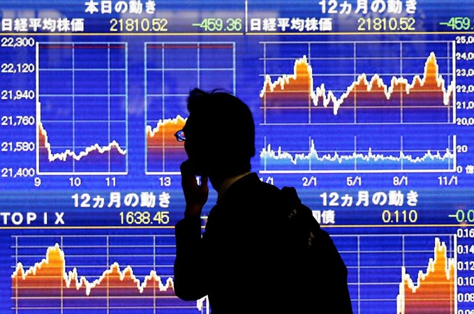 Seorang pria melihat papan elektronik yang menunjukkan rata-rata indeks Nikkei Jepang di Tokyo, Jepang, 13 November 2018. - REUTERS/Toru Hanai