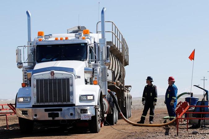 Sebuah truk tangki yang digunakan untuk mengangkut produk minyak beroperasi di fasilitas minyak dekat Brooks, Alberta, Kanada 18 April 2018. - REUTERS/Todd Korol