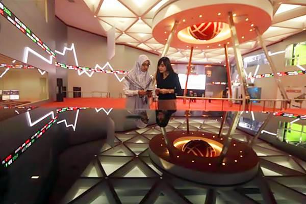 Karyawati berbincang di dekat layar pergerakan Indeks Harga Saham Gabungan (IHSG), di gedung Bursa Efek Indonesia, Jakarta, Jumat (21/7). - JIBI/Nurul Hidayat