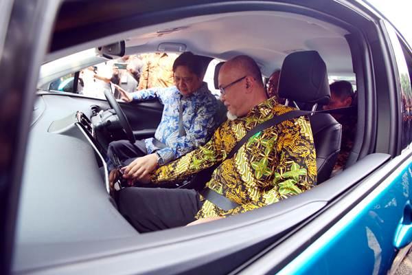 Menteri Perindustrian Airlangga Hartarto (kiri) didampingi Presiden Direktur Toyota Motor Manufacturing Indonesia Warih Andang Tjahjono mencoba mobil listrik saat acara Kickoff Electrified Vehicle Comprehensive Study di Jakarta, Rabu (4/7/2018). - JIBI/Abdullah Azzam
