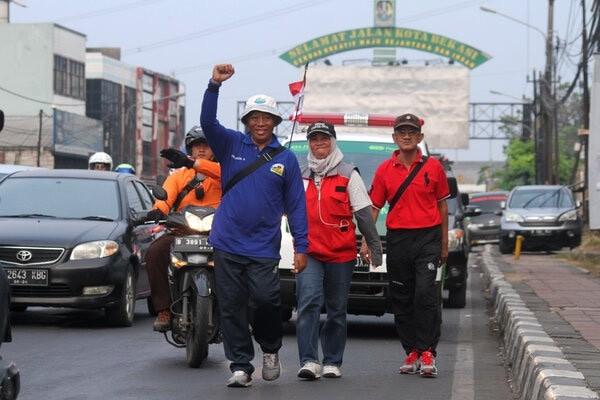 Rachmat Komaruddin (kiri) penyintas sakit stroke melakukan aksi berjalan kaki dari Bandung menuju Jakarta saat melintasi Jalan Juanda, di Bekasi, Jawa Barat, Senin (28/10/2019). Aksi jalan kaki menuju Jakarta yang menempuh waktu lima hari tersebut guna mengikuti peringatan Hari Stroke Sedunia pada 29 Oktober 2019 di Jakarta. - Antara/Risky Andrianto