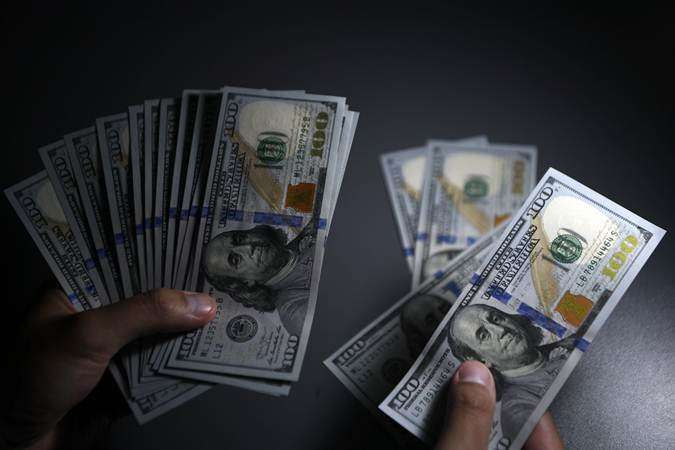 Seorang pembeli menghitung uang Dolar Amerika Serikat yang ditukarnya di gerai penukaran valuta asing, Jakarta, Senin (15/7/2019). - ANTARA/Puspa Perwitasari