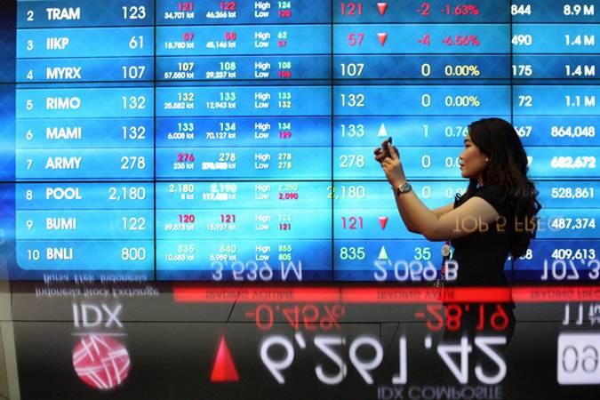 Pengunjung menggunakan ponsel di dekat papan elektronik yang menampilkan perdagangan harga saham di BEI, Jakarta - Bisnis/Dedi Gunawan