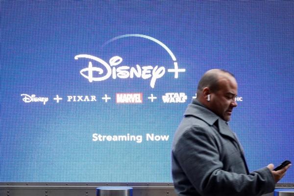 Seorang pria melihat layar handphone saat melintas di depan layar iklan Disney, layanan streaming Walt Disney di New York City Amerika Serikat, Selasa (12/11/2019) - Reuters/Brendan McDermid