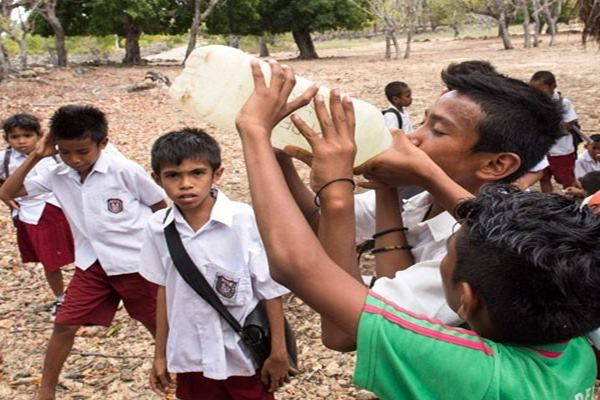 Anak Sekolah Siswa SD Inpres Deranitan berebut air minum seusai bermain bola di desa Dolasin, Rote Barat Daya, Nusa Tenggara Timur. - Antara