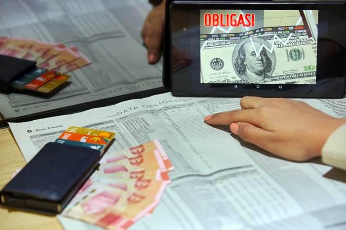 Karyawan mencari informasi tentang obligasi di Jakarta, Rabu (17/7/2019). - Bisnis/Abdullah Azzam