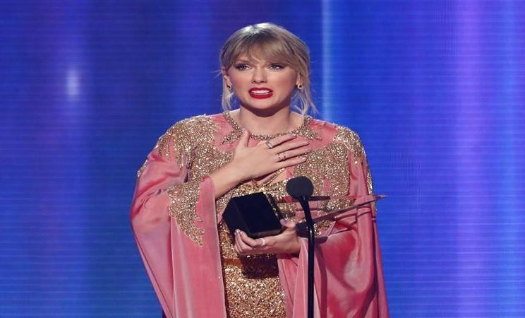 Taylor Swift menerima penghargaan Artist of the Year. - Reuters