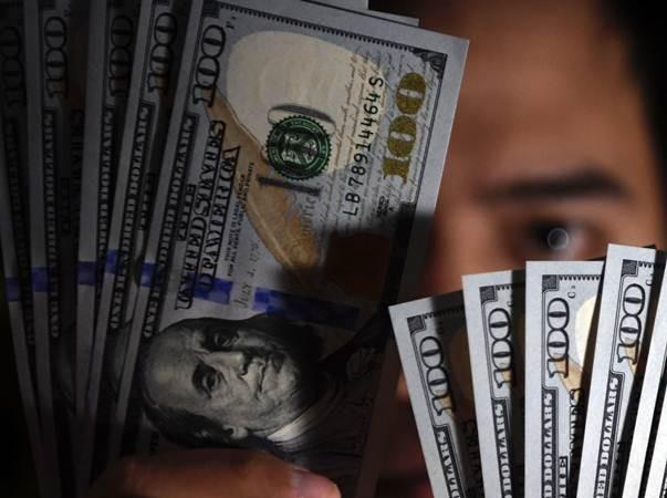 Seorang pembeli menunjukkan uang Dolar Amerika Serikat yang ditukarnya di gerai penukaran valuta asing, Jakarta, Senin (15/7/2019). - ANTARA/Puspa Perwitasari