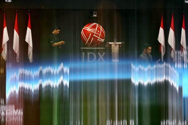 Karyawan berkomunikasi di dekat monitor informasi Indeks Harga Saham Gabungan (IHSG) di Bursa Efek Indonesia Jakarta - Bisnis/Nurul Hidayat