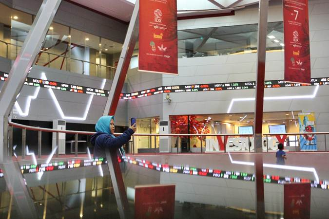 Pengunjung menggunakan smartphone di dekat papan elektronik yang menampilkan perdagangan saham di BEI, Jakarta - Bisnis/Dedi Gunawan