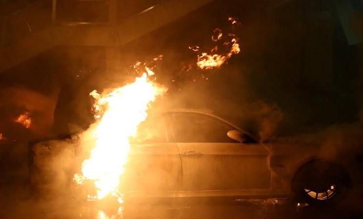 Sebuah mobil terbakar selama bentrokan antara demonstran anti-pemerintah dan polisi anti huru hara di Tsim Sha Tsui, di Hong Kong. - Reuters