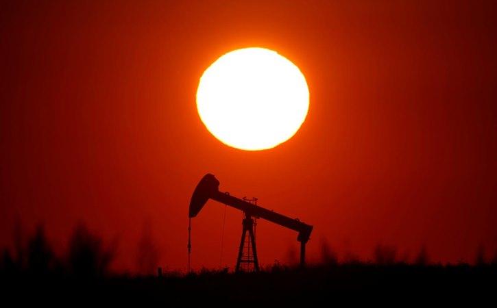 Matahari terbenam di belakang sebuah pompa minyak di luar Saint-Fiacre, dekat Paris, Prancis Selasa (17/9/2019). - REUTERS/Christian Hartmann
