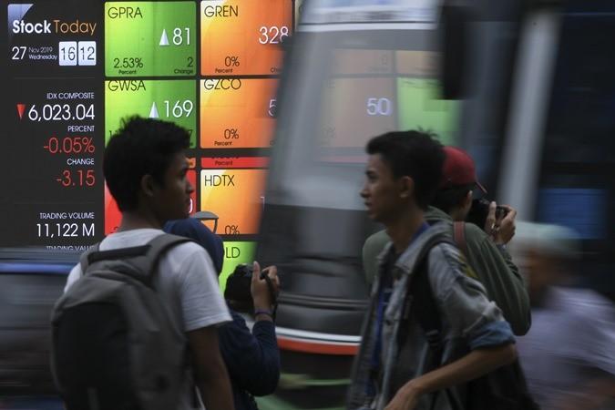 Calon penumpang menunggu bus Transjkarta dengan latar belakang layar pergerakan saham PT Bursa Efek Indonesia di jalan Jenderal Sudirman Jakarta, Rabu (27/11/2019). - ANTARA/Wahyu Putro