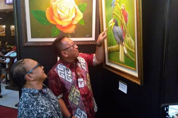 Kepala Dinas Pemuda, Olahraga dan Pariwisata (Disporapar) Jawa Tengah Sinung Rachmadi( kanan) menunjuk lukisan dalam peringatanHari Internasional Penyandang Cacat (Hipenca) 2019 di Mal Ciputra Semarang, Selasa(3/12). - Bisnis/Alif Nazzala Rizqi