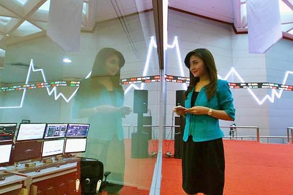 Pengunjung mengamati papan elektronik yang menunjukkan pergerakan indeks harga saham gabungan (IHSG), di gedung Bursa Efek Indonesia, Jakarta, Kamis (3/8). - JIBI/Dwi Prasetya