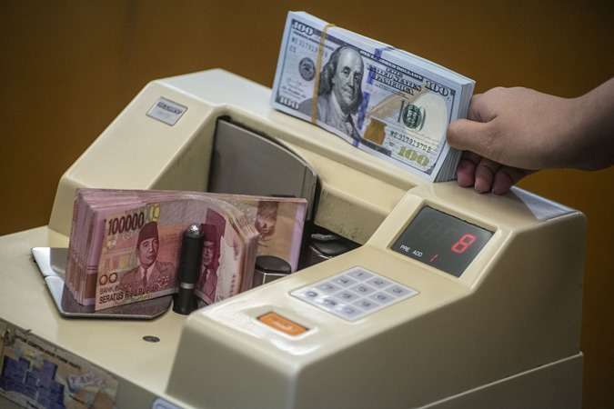 Petugas mengitung uang rupiah di salah satu gerai penukaran uang asing di Jakarta, Rabu (27/11/2019). - ANTARA/Aprillio Akbar