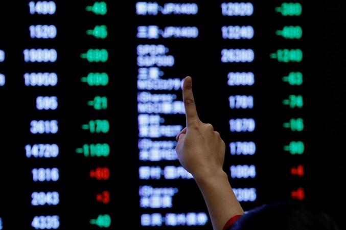 Seorang wanita menunjuk ke papan elektronik yang menunjukkan harga saham ketika dia berpose di depan dewan setelah upacara pembukaan Tahun Baru di Tokyo Stock Exchange (TSE), Tokyo, Jepang, 4 Januari 2019. - REUTERS/Kim Kyung/Hoon