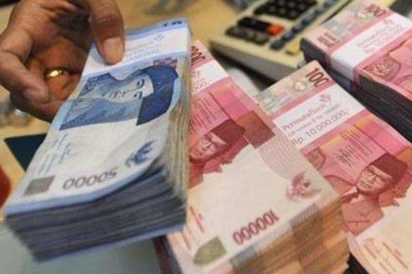 Ilustrasi: Seorang karyawan bank tengah merapikan uang - Antara