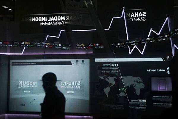 Pengunjung melintas di samping papan penunjuk Indeks Harga Saham Gabungan (IHSG) di gedung Bursa Efek Indonesia (BEI), Jakarta - Bisnis/Felix Jody Kinarwan