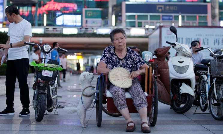 Seorang wanita 68 tahun dengan stroke duduk di roda tiga saat dia beristirahat di alun-alun kota di Weifang, provinsi Shandong, China, 24 Juli 2019. - REUTERS / Jason Lee