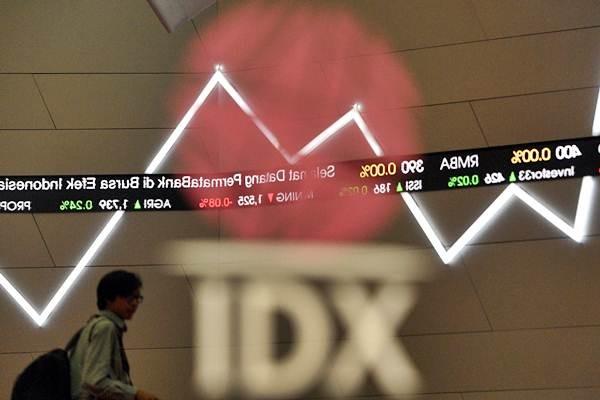 Karyawan melintas di dekat monitor pergerakan Indeks Harga Saham Gabungan (IHSG) di Bursa Efek Indonesia, Jakarta, Senin (11/9). - ANTARA/Sigid Kurniawan