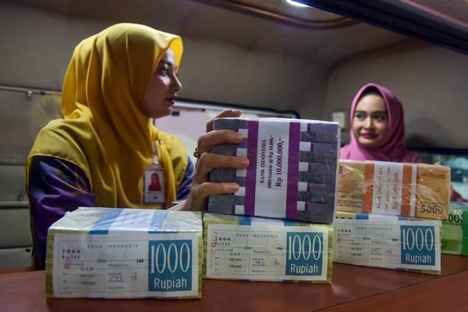 Pegawai Bank Riau-Kepri menyiapkan uang kertas baru saat membuka layanan penukaran uang oleh Bank Indonesia (BI), BRI dan Bank Riau-Kepri di Kota Pekanbaru, Riau, Senin (13/5/2019). - ANTARA/FB Anggoro