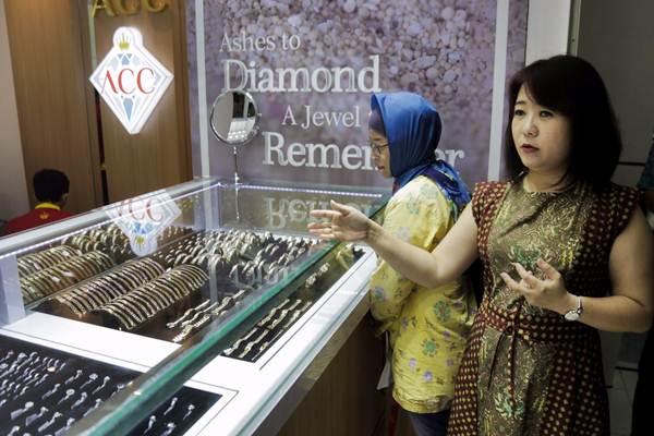 Direktur Utama PT Hartadinata Abadi Tbk Sandra Sunanto (kanan) memperlihatkan koleksi perhiasan emas di toko emas ACC, di Blok M Square, Jakarta, Selasa (5/9). - JIBI/Felix Jody Kinarwan