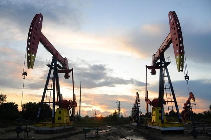 Pumpjacks terlihat saat matahari terbenam di ladang minyak Daqing di provinsi Heilongjiang, China 22 Agustus 2019. - REUTERS/Stringer