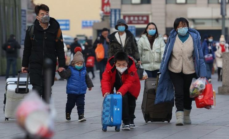 Warga mengenakan masker di stasiun kereta di Beijing, China, Jumat (24/1/2020). - Yomiuri Shimbun via Reuters