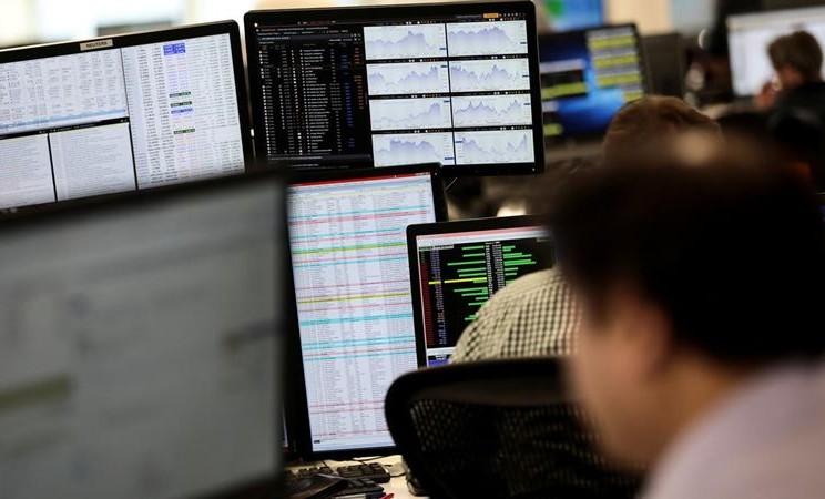 Trader melihat monitor perdagangan pasar saham di London. - Reuters