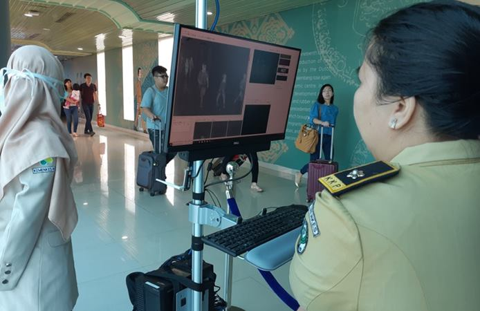Petugas Kantor Pelabuhan Palembang memeriksa suhu tubuh penumpang di Bandara SMB II Palembang menggunakan thermal scanner. - Bisnis / Dinda Wulandari