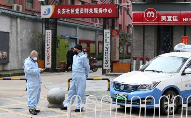 Pengemudi taksi memakai pakaian pelindung khusus berada di depan area perumahan setelah wabah virus corona di Wuhan, Provinsi Hubei, China. Foto diambil (28/1 - 2020). China Daily via Reuters