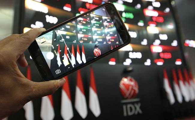 Pengunjung menggunakan ponsel memotret papan elektronik yang menampilkan pergerakan harga saham di Jakarta, Jumat (31/1/2020). Bisnis - Dedi Gunawan