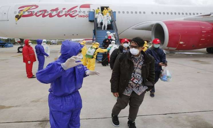 Petugas medis mengarahkan Warga Negara Indonesia (WNI) dari Wuhan, China yang telah disemprot cairan disinfektan setibanya di Bandara Hang Nadim, Batam, Kepulauan Riau, Minggu (2/2/2020). Sebanyak 238 orang WNI dari Wuhan, China tersebut selanjutnya dipindahkan ke Natuna untuk menjalani observasi selama kurang lebih dua minggu guna memastikan kesehatannya dan terbebas dari virus corona.  - Antara