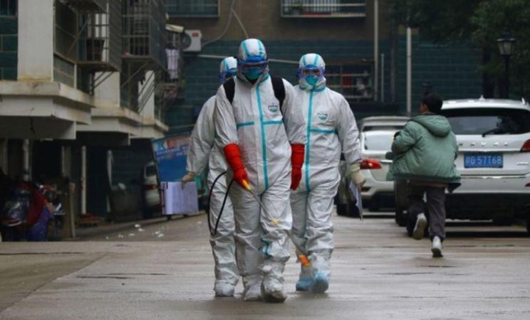 Pekerja dari Departemen Pengendalian dan Pencegahan Penyakit mendisinfeksi area perumahan setelah wabah virus Corona, di Ruichang, Provinsi Jiangxi, China, pada Sabtu (25/1/2020). - Reuters