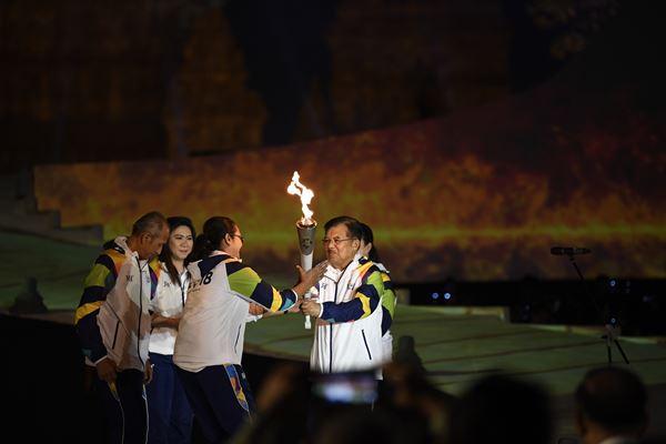 Wapres Jusuf Kalla (kanan) disaksikan legenda bulu tangkis Indonesia Susi Susanti (kedua kiri) dan mantan atlet tenis Yustedjo Tarik (kiri) menyerahkan api obor Asian Games 2018 yang telah disatukan kepada mantan atlet bulu tangkis Finarsih (kedua kanan) saat Asian Games 2018 Torch Relay Concert di Kompleks Candi Prambanan, Sleman, DI Yogyakarta, Rabu (18/7). Penyatuan api obor dari India dan Mrapen tersebut menandai dimulainya perjalanan api obor Asian Games 2018. - ANtara