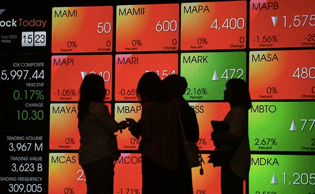 Pengunjung melintas didekat papan elektronik yang menampilkan pergerkan Indeks Harga Saham Gabngan di Bursa Efek Indonesia, Jakarta, Jumat (7/2/2020) Binsis - AbdurachmanAbdurachman