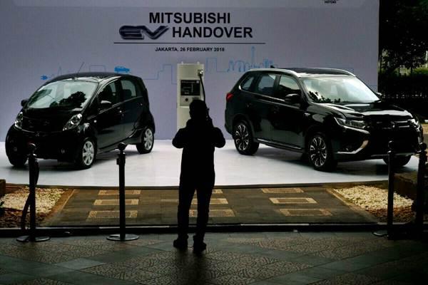 Karyawan mengamati mobil hybrid dan mobil listrik sebelum prosesi penyerahan kepada pemerintah Indonesia di Jakarta, Senin (26/2/2018). Mitsubishi Motors memberikan 8 unit Mitsubishi Outlander PHEV model SUV plug-in Hybrid, 2 unit mobil listrik i-MiEV dan 4 unit quick charger kepada pemerintah indonesia. - JIBI/Nurul Hidayat