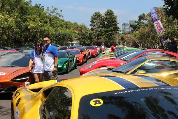 Dua peserta berfoto di depan 72 supercar yang diparkir di Hilton Garden Inn Bali Ngurah Rai Airport. - Bisnis.com/ Ni Putu Eka Wiratmini