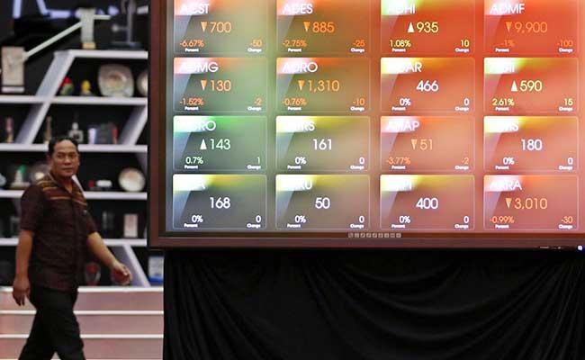 Karyawan melintas didekat layar monitor perdagangan Indeks Saham Gabungan (IHSG) di Bursa Efek Indonesia, Jakarta, Senin (17/2/2020). Bisnis - Eusebio Chrysnamurti