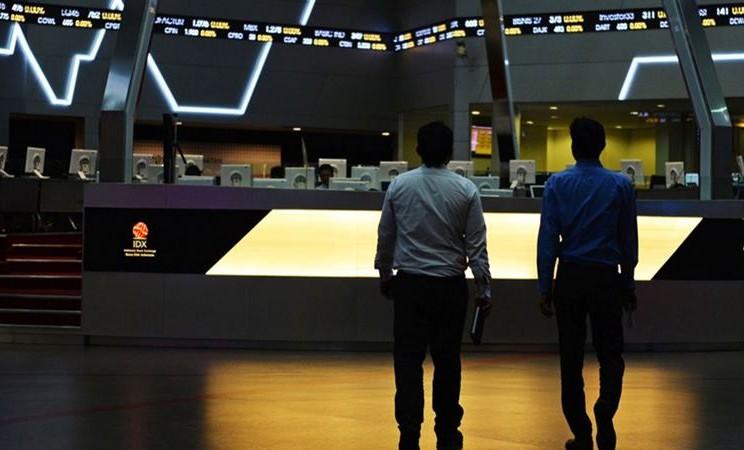 Trader berjalan saat ticker menampilkan harga saham di dalam Bursa Efek Indonesia (BEI) di Jakarta, Indonesia. -  Dimas Ardian / Bloomberg