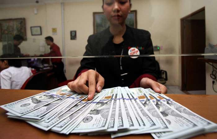 Karyawan menghitung uang di salah satu gerai penukaran uang di Jakarta, Senin (12/8/2019). Bisnis - Arief Hermawan P