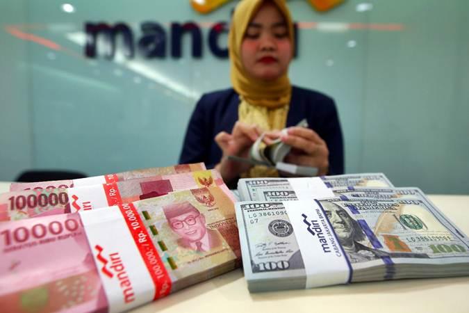 Karyawati Bank Mandiri menghitung mata uang dolar AS dan rupiah di Jakarta, Selasa (12/2/2019). - Bisnis/Abdullah Azzam