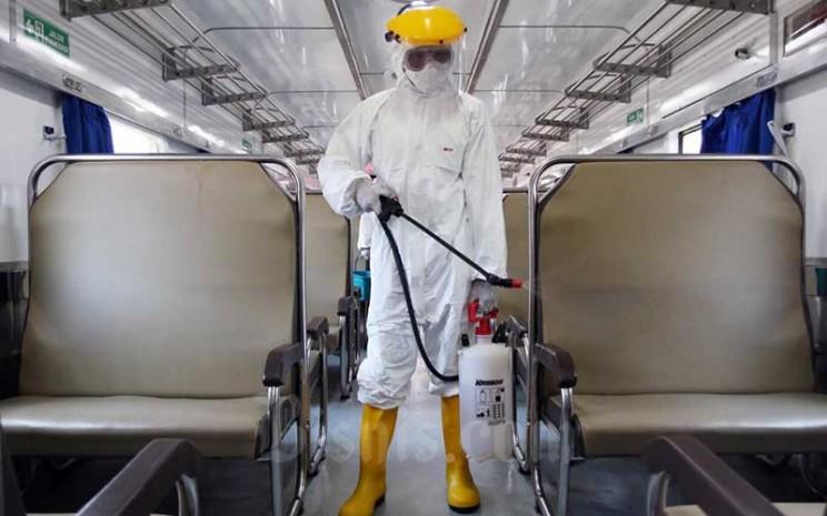 Petugas saat melakukan penyemprotan disinfektan pada gerbong kereta api di Stasiun Pasar Senen, Jakarta, Minggu (15/3/2020). Bisnis - Eusebio Chrysnamurti\\n