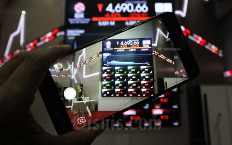Pengunjung menggunakan smarphone memotret papan elektronik yang menampilkan perdagangan harga saham di Bursa Efek Indonesia di Jakarta, Seni (16/3/2020). Bisnis - Dedi Gunawan