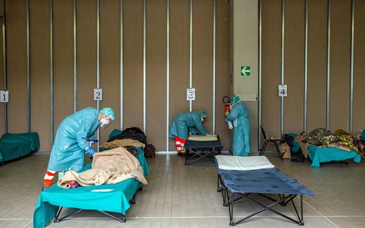 Tenaga medis merawat pasien di tenda dan bangunan darurat yang dibuat untuk membantu sistem perawatan kesehatan di kawasan rumah sakit di Brescia, Italia, Jumat (13/3/2020).  Penyebaran wabah virus corona (Covid-19) di Italia cukup signifikan dengan pertumbuhan jumlah kematian pasien yang mencapai 14 persen. Bloomberg - Francesca Volpi