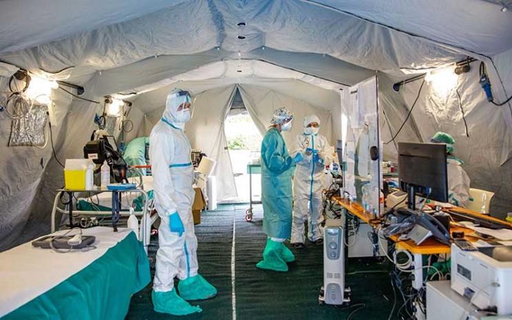 Tenaga medis bekerja di tenda dan bangunan darurat yang dibuat untuk membantu sistem perawatan kesehatan di kawasan rumah sakit di Brescia, Italia, Jumat (13/3/2020). Penyebaran wabah virus corona (Covid-19) di Italia cukup signifikan dengan pertumbuhan jumlah kematian pasien yang mencapai 14 persen. Bloomberg - Francesca Volpi